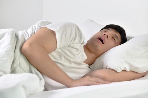 Giovane uomo asiatico che dorme e russa rumorosamente sdraiato a letto