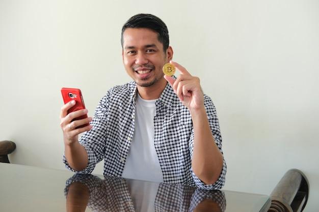 Giovane uomo asiatico che sorride felice mentre tiene il telefono cellulare e mostra il suo bitcoin d'oro