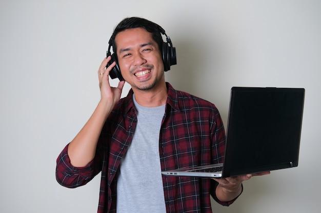 Giovane uomo asiatico che sorride felice mentre indossa le cuffie e tiene in mano un computer portatile