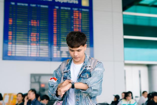 Giovane uomo asiatico in piedi vicino all'orario della compagnia aerea e toccando il suo orologio