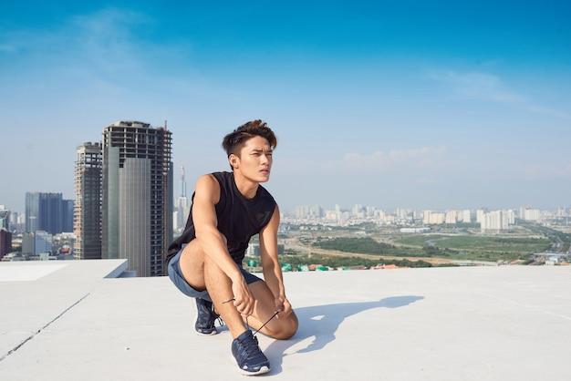 Il giovane uomo asiatico lega i lacci delle scarpe sportive prima di correre all'aperto