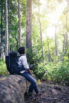 Viaggiatore del giovane uomo asiatico con lo zaino che cattura foto sulle montagne in tailandia.