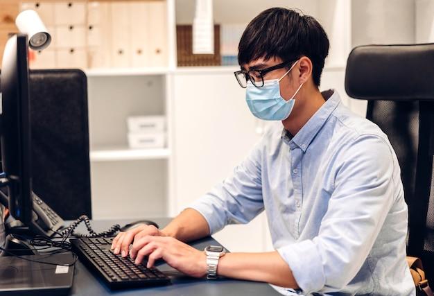Giovane uomo asiatico che utilizza computer portatile lavorando e videoconferenza chat online in quarantena per coronavirus che indossa maschera protettiva con allontanamento sociale a casa. lavoro da casa
