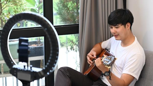 Giovane video blogger asiatico che suona la chitarra e registra contenuti video per il suo blog.