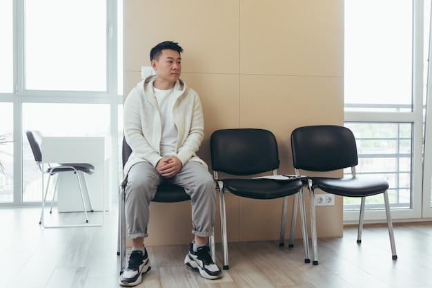 Giovane uomo asiatico in attesa di un colloquio o di un incontro seduto nel corridoio nella sala d'attesa. studente o concorrente alla reception per esame o occupazione hr. paziente maschio in ufficio una clinica ospedaliera