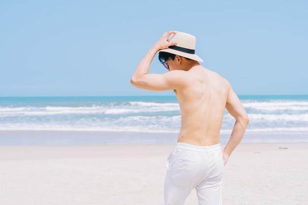 Giovane uomo asiatico che cammina sulla spiaggia
