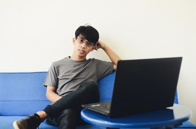 Giovane uomo asiatico che indossa una camicia di cenere davanti al laptop seduto sul divano