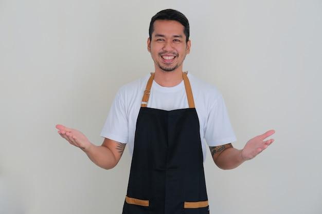 Giovane uomo asiatico che indossa un grembiule da barista sorridente amichevole mentre fa il gesto di saluto