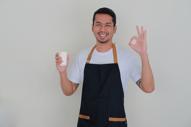 Giovane uomo asiatico che indossa un grembiule da barista sorridente amichevole mentre tiene in mano un bicchiere