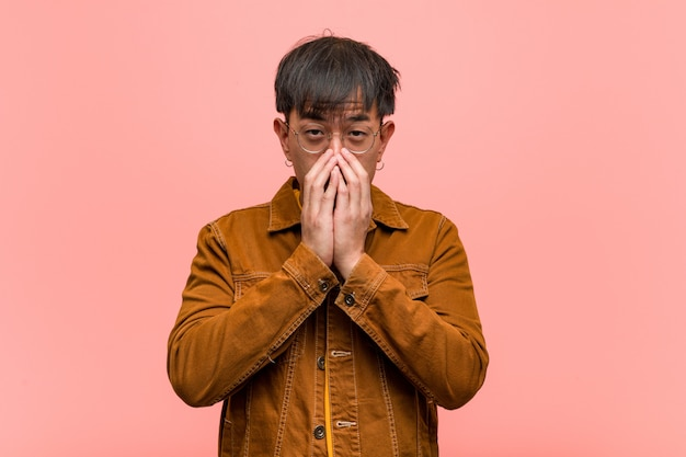 Giovane uomo asiatico che indossa una giacca nascosta molto spaventata e impaurita