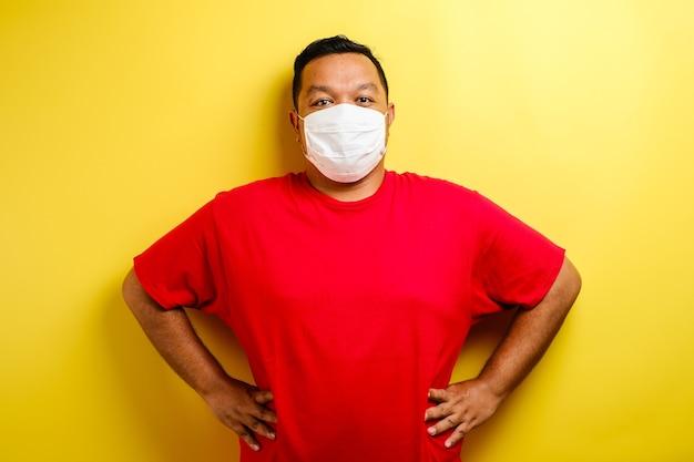 Un giovane uomo asiatico che indossa una maschera medica che protegge dalla diffusione della malattia da virus corona. primo piano di un uomo con una maschera chirurgica sul viso su sfondo giallo