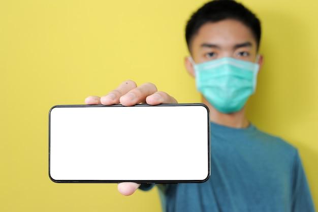 Giovane uomo asiatico che indossa la maschera protettiva che mostra smartphone con schermo vuoto, isolato su giallo