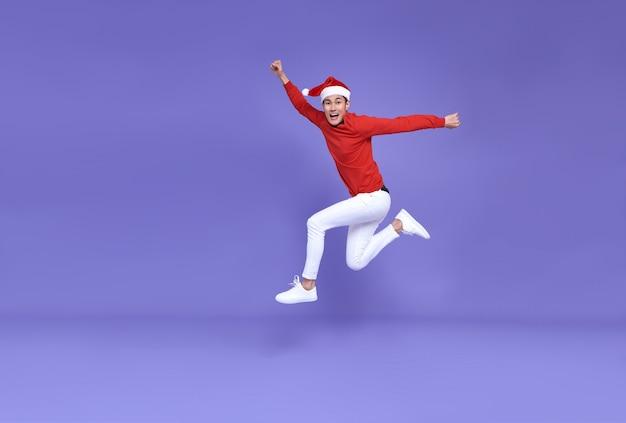 Giovane uomo asiatico che indossa il cappello della santa che salta e sorride