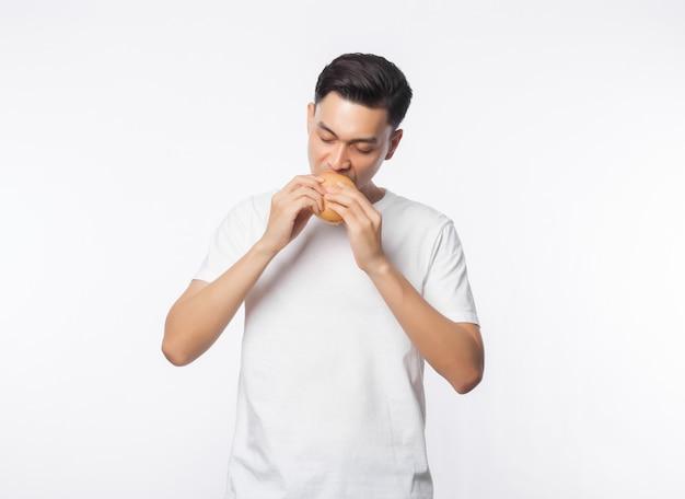Giovane uomo asiatico in maglietta bianca che mangia hamburger