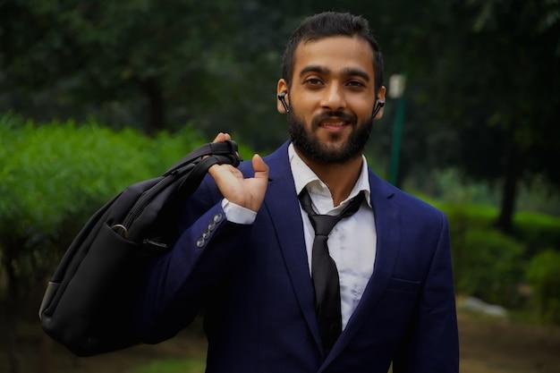 Un giovane asiatico con una borsa e vestito come un uomo d'affari