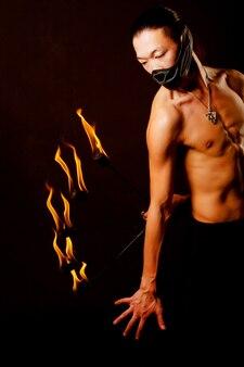 Giovane uomo asiatico con spettacolo di fuoco