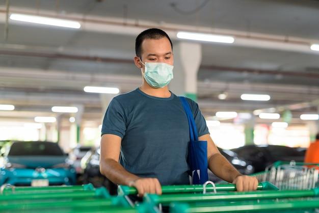 Giovane uomo asiatico con la maschera che tiene il carrello della spesa al parcheggio