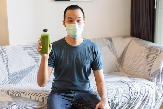Giovane uomo asiatico con maschera che mostra frullato verde per una sana alimentazione a casa in quarantena