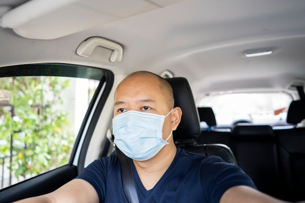 Giovane uomo asiatico con maschera protettiva alla guida di un'auto