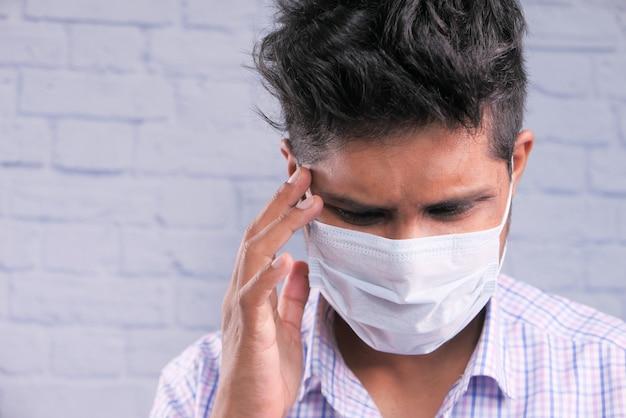 Un giovane uomo asiatico con maschera protettiva in faccia sentirsi triste