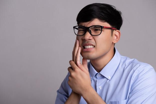 Giovane uomo asiatico con denti sensibili o mal di denti. concetto di assistenza sanitaria.