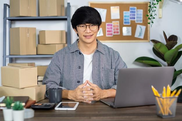 Giovane uomo asiatico che lavora all'ufficio di servizio di distribuzione