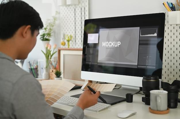 Giovane uomo asiatico che lavora da casa su un computer