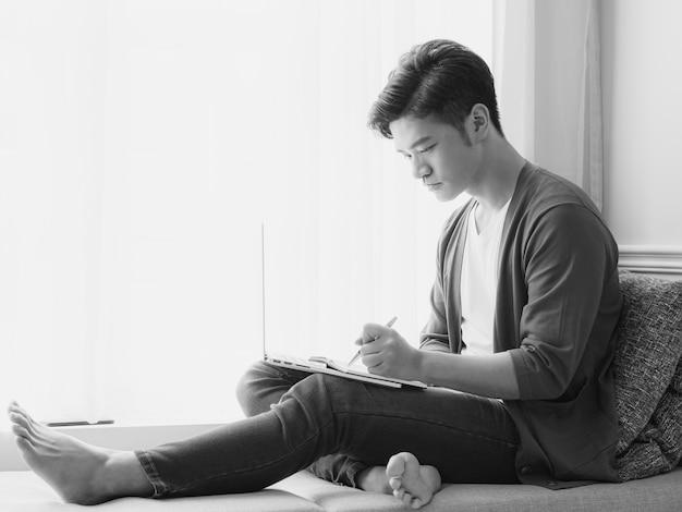 Giovane uomo asiatico che scrive in un libro quando usa il laptop