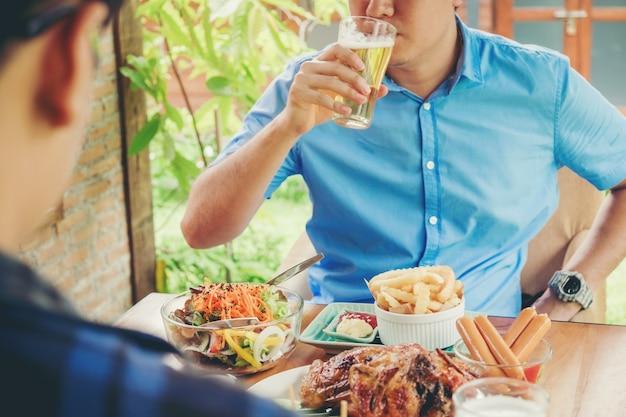 Il giovane asiatico equipaggia bevendo la birra e mangiando gli alimenti