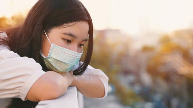 Giovane donna millenaria asiatica del gen z che sta al tetto che si sente annoiata e che esamina paesaggio urbano mentre indossando maschera