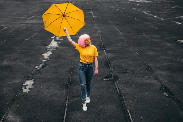 Giovani asiatici millennial hipster in abito elegante che trasportano ombrello giallo
