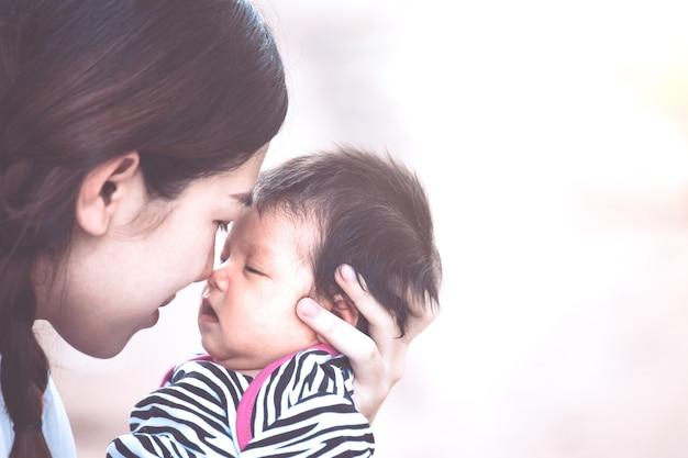 Giovane madre asiatica che abbraccia e bacia la sua neonata con amore nel tono di colore dell'annata