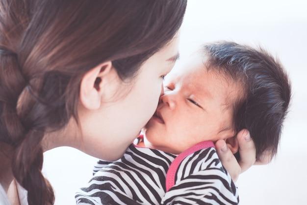Giovane madre asiatica che abbraccia e bacia la sua neonata con amore
