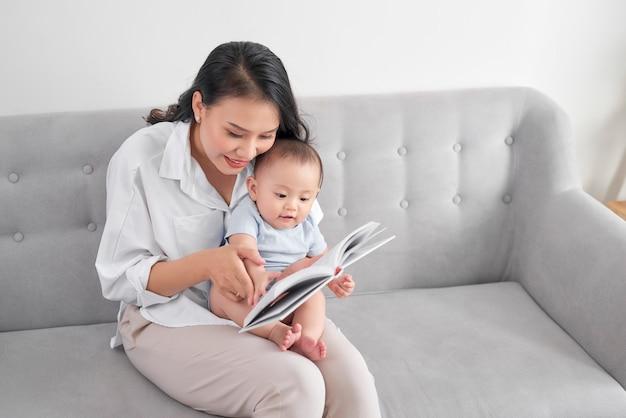 Libro di lettura della giovane madre asiatica al bambino. dolce momento.