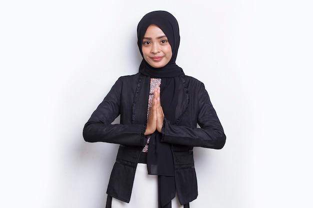 La giovane donna d'affari musulmana asiatica mostra il gesto di benvenuto isolato su sfondo bianco