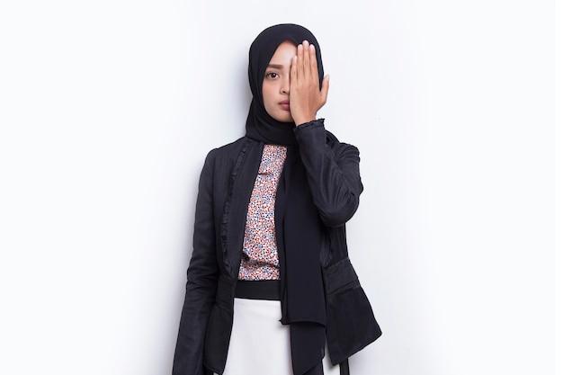 Giovane donna musulmana asiatica che copre un occhio con la mano isolata su sfondo bianco