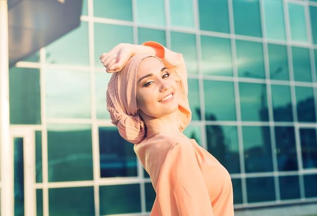 Giovane donna musulmana asiatica nel sorriso della sciarpa capa all'aperto