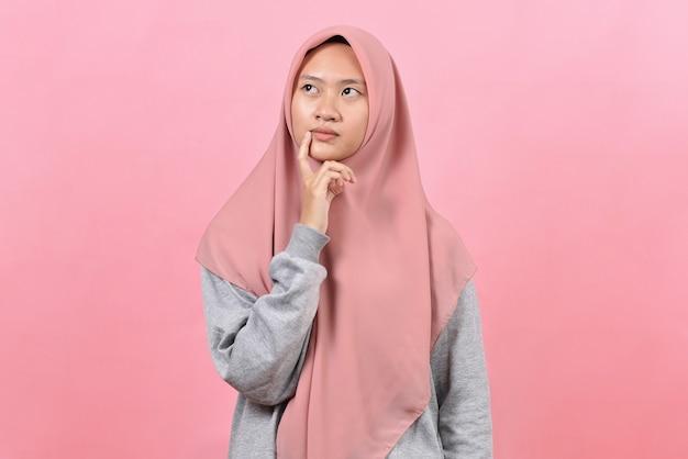 Giovane donna musulmana asiatica che esamina uno spazio della copia o che pensa un'idea; isolato in sfondo rosa