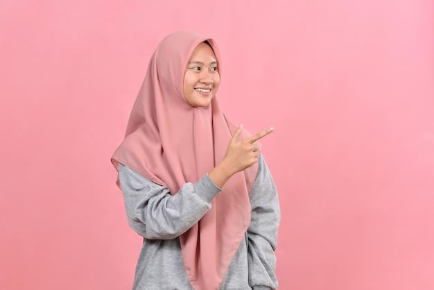 La giovane donna musulmana asiatica sorridente punta da parte sullo spazio della copia mostra che la pubblicità indossa abiti casuali musulmani