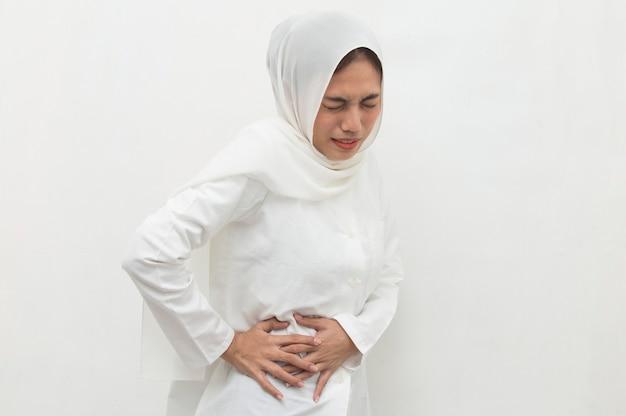 Giovane donna musulmana asiatica che soffre di mal di schiena e dolore lombare in vita