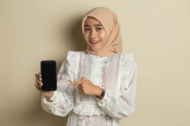 Giovane donna musulmana asiatica che indossa l'hijab che mostra il telefono cellulare dello schermo in bianco