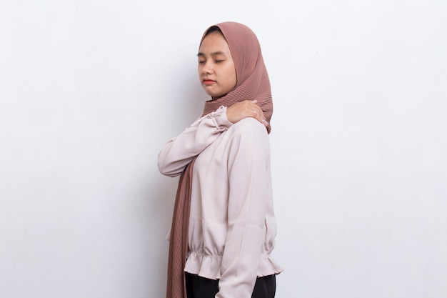 Giovane donna musulmana asiatica con dolore al collo e alla spalla e concetto medico di lesioni