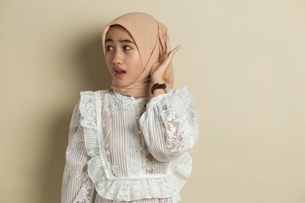 Le giovani donne musulmane asiatiche con l'hijab stanno ascoltando