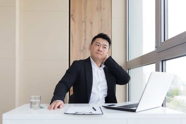 Il giovane impiegato asiatico che soffre di mal di testa al lavoro in ufficio beve la pillola della medicina con acqua. l'uomo malato in giacca e cravatta al computer al chiuso con forti dolori usa il farmaco sul posto di lavoro