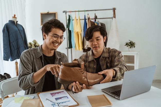 Uomo d'affari giovani asiatici in chat sul prodotto di scarpe