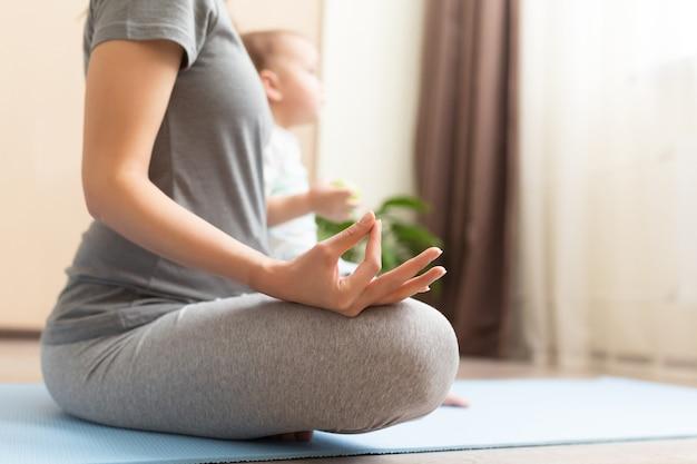 Giovane donna incinta asiatica che medita a casa con suo figlio figlio ragazzo. concetto di maternità sana