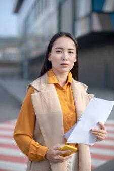 Giovane donna graziosa asiatica che porta i documenti beige della tenuta del cardigan