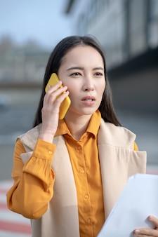 Cardigan beige da portare della giovane donna graziosa asiatica che sembra serio