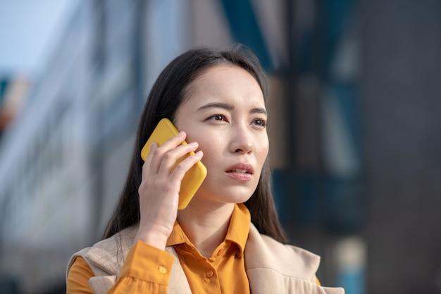 Giovane donna graziosa asiatica che indossa cardigan beige che sembra sollecitata