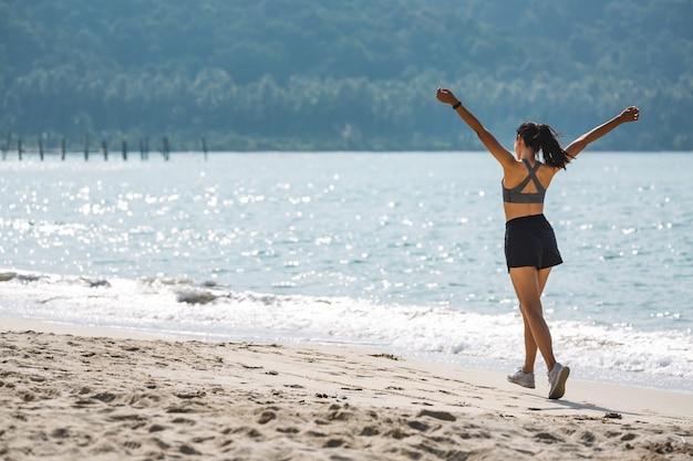 La giovane donna asiatica del corridore funziona sulla spiaggia in tailandia, sullo sport e sul concetto sano di vacanza